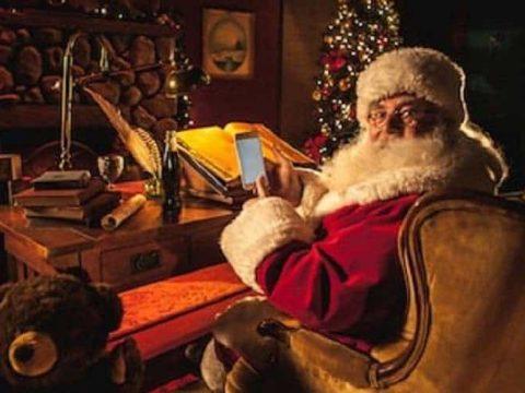 santa claus using a smartphone to gamble at his desk